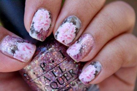 unhas decoradas com flores e fundo rosa glitter
